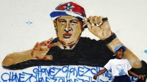 A boy plays next to graffiti depicting Venezuelan President Hugo Chavez as a rap singer in Petare in the suburbs of Caracas on September 13, 2012. REUTERS/Jorge Silva