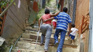 "Alcide Arregocete, who has a prosthesis on her leg, up the stairs with the help of a crutch in Las Mayas slum in Caracas May 28, 2011. Despite being in power for 12 years and bringing plenty of new schools and clinics to poor areas, Chavez has failed to fix Venezuela's housing shortfall -- currently at 2 million units. That, say critics, demonstrates the failure of socialism in Venezuela, where the 500,000 new homes built during Chavez's rule, about two-thirds by the private sector, is no better than the rate of construction under his predecessors. Not surprisingly, Chavez has sought to take the initiative with a new ""Grand Housing Mission"" -- his eighth such construction plan -- aiming to build 2 million new units by 2017 with funds available from higher global oil prices. To match Feature VENEZUELA-HOUSING/    Picture taken May 28, 2011.   REUTERS/Jorge Silva (VENEZUELA - Tags: POLITICS BUSINESS SOCIETY) - RTR2N78X"