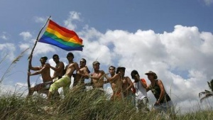 "Men pose with a gay pride flag during the opening of the gay and lesbian community's summer at a beach on the outskirts of Havana June 14, 2008. Much has changed in Cuba since the 1960s when homosexuals were sent to work camps, or the 1970s when gay men and women were denied certain jobs as ""ideological deviants."" Cuba, in the latest change since President Raul Castro took office, has allowed doctors to perform sex change operations and parliament is studying proposals to legalize same-sex unions.  REUTERS/Claudia Daut (CUBA)"