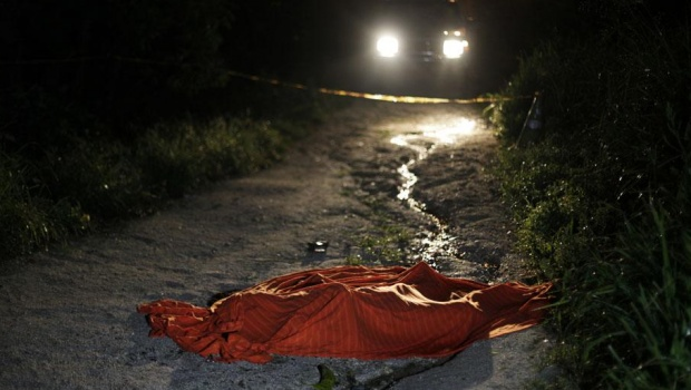 The covered-up body of a young man who had been shot dead is seen at a crime scene in San Pedro Sula March 28, 2013. San Pedro Sula, the country's second largest city after Tegucigalpa, has a homicide rate of 169 per 100,000 people and was named the world's most violent city for a second year in a row. Lax laws allow civilians to own up to five personal guns, and arms trafficking has flooded the country with nearly 70% illegal firearms. 83.4% of homicides are by firearm compared to 60% in the United States. Picture taken March 28, 2013           REUTERS/Jorge Cabrera (HONDURAS  - Tags: CRIME LAW CIVIL UNREST HEALTH)