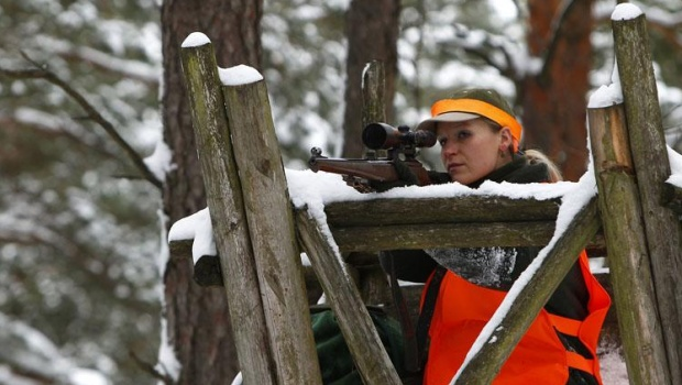 Hunter Ramona Pohl-Uebel sits at a raised platform while taking part in a driven hunt event at the U.S. military training ground in Hohenfels near Regensburg December 14, 2012. REUTERS/Michaela Rehle