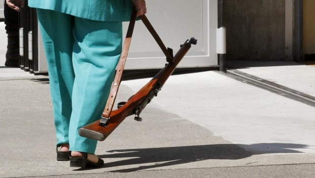 A resident carries a vintage Swiss army rifle to be handed over at a police station in Zurich May 21, 2011. The Canton of Zurich is collecting unwanted weapons and ammunition from civilians and those who previously served in the defence sector. The firearms will be destroyed.  REUTERS/Arnd Wiegmann (SWITZERLAND - Tags: SOCIETY) - RTR2MP1S