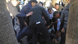 A man is detained by police and local security after shooting on the sidelines of the Cannes Film Festival near the Grand Journal de Canal+ television studio set on the Croisette in Cannes May 17, 2013. REUTERS/Nathan Gourdol
