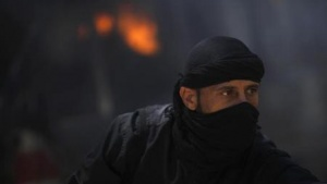 A fighter from the Islamist Syrian rebel group Jabhat al-Nusra is seen in front of a burning vehicle, caused by what activists said were missiles fired by a Syrian Air Force fighter jet from forces loyal to Syria's President Bashar al-Assad, at their base in Raqqa province, east Syria, May 12, 2013. REUTERS/Hamid Khatib