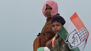 Supporters holding flags of ruling Congress party leave after attending an election campaign rally by Rahul Gandhi at Hardoi district in Uttar Pradesh January 28, 2012. REUTERS/Adnan Abidi/Files