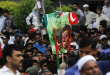 A supporter of Pakistan's Muttahida Quami Movement (MQM) holds a dirt-stained T-shirt with an image of Imran Khan, leader of the Pakistan Tehreek-e-Insaf (PTI), during a protest against him in Karachi May 20, 2013. REUTERS/Athar Hussain