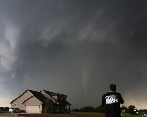Storm chaser videographer and photographer Brad Mack records a tornado near a home in South Haven, in Kansas May 19, 2013. A massive storm front swept north through the central United States on Sunday, hammering the region with fist-sized hail, blinding rain and tornadoes, including a half-mile wide twister that struck near Oklahoma City. News reports said at least one person had died.  REUTERS/Gene Blevins
