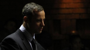 Oscar Pistorius stands in the dock ahead of court proceedings at the Pretoria magistrates court February 22, 2013. REUTERS/Siphiwe Sibeko/Files