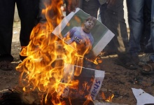 Demonstrators burn a poster of former India test bowler Shanthakumaran Sreesanth during a protest in Ahmedabad May 16, 2013. REUTERS/Amit Dave