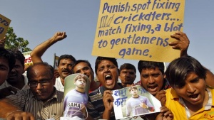 Demonstrators shout slogans as they hold a placard and posters of former India test bowler Shanthakumaran Sreesanth during a protest in Ahmedabad May 16, 2013. REUTERS/Amit Dave
