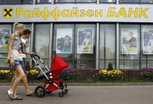 Pedestrians walk past a Raiffeisen Bank branch in Moscow May 19, 2013.  REUTERS/Sergei Karpukhin