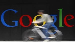 An employee rides her bike past a logo next to the main entrance of the Google building in Zurich July 9, 2009. REUTERS/Christian Hartmann/Files