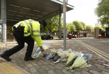 A police officer arranges floral tributes outside the Royal Military Barracks, near the scene where a British soldier was killed in Woolwich, southeast London May 23, 2013.  REUTERS/Luke MacGregor