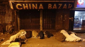 Homeless people sleep on a roadside in a cold morning in the old quarters of Delhi January 13, 2011. REUTERS/Adnan Abidi/Files