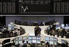 Traders work at their desks in front of the DAX board at the Frankfurt stock exchange May 24, 2013.  REUTERS/Remote/Marte Kiesling