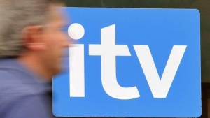A man passes ITV television studios in central London August 3, 2010. REUTERS/Toby Melville/Files