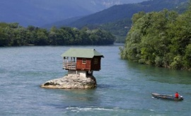 A man powers a boat near a house built on a rock on the river Drina near the western Serbian town of Bajina Basta, about 160km from the capital Belgrade May 22, 2013. REUTERS/Marko Djurica/Files