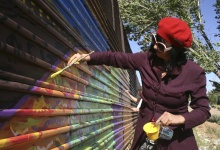 Artist Gretchen Baer paints on a fence marking the U.S. border in Naco, Mexico April 17, 2013. REUTERS/Tim Gaynor