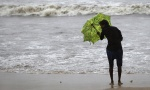 A man holds an umbrella to shield himself from the rain on a beach in Mumbai June 13, 2013. REUTERS/Danish Siddiqui