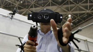 "A visitor tries out the ""HEWDD (High End Wearable Display Device)-1080"", which allows the user to perceive virtual worlds, at the 3D and Virtual Reality Expo in Tokyo June 20, 2012.  REUTERS/Yuriko Nakao/Files"