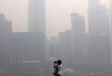A woman takes photos of the hazy skyline of Singapore June 19, 2013. REUTERS/Edgar Su