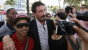 Computer software pioneer John McAfee (C) poses with tourists as he speaks with reporters outside his hotel in Miami Beach, Florida December 13, 2012. REUTERS/Joe Skipper