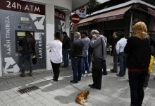 People queue up to make a transaction at an ATM outside a branch of Laiki Bank in Nicosia March 21, 2013. REUTERS/Yannis Behrakis
