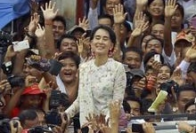 Myanmar pro-democracy leader Aung San Suu Kyi smiles to supporters as she leaves the National League for Democracy party headquarters after attending her 68th birthday ceremony in Yangon June 19, 2013. REUTERS/Soe Zeya Tun