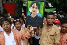 Supporters hold a picture of Myanmar pro-democracy leader Aung San Suu Kyi as they celebrate at her 68th birthday ceremony in front of the party headquarters of National Leage for Democracy in Yangon June 19, 2013. REUTERS/Soe Zeya Tun