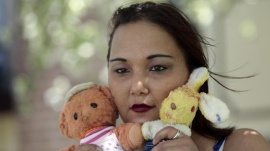 Inga Whatcott, adopted from Russia, holds two stuffed dolls she saved from her orphanage in Russia, outside her apartment in Battle Creek, Michigan, in this May 26, 2013 photograph. REUTERS/ Rebecca Cook