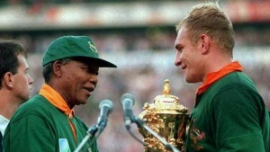 South African President Nelson Mandela (R) hands over the William Webb Ellis Cup to Springbok captain Francois Pienaar after his team defeated New Zealand in the Rugby World Cup final June 24, 1995. REUTERS/Files