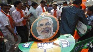 A supporter wearing a cap carrying a picture of Gujarat's chief minister and Hindu nationalist Narendra Modi, the prime ministerial candidate for India's main opposition Bharatiya Janata Party (BJP), attends the celebrations outside the party's headquarters in Ahmedabad December 8, 2013. REUTERS/Amit Dave