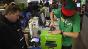 A man buys an XBOX One video game console at a ToysRUs store during their Black Friday Sale in New York November 28, 2013. REUTERS/Carlo Allegri/Files