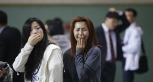 The mother (R) of a passenger who was on a sinking ferry reacts as she finds her son at a gym where rescued passengers gather in Jindo April 16, 2014. REUTERS/Kim Hong-Ji