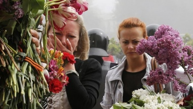 Women bring flowers in memory of people killed in recent street battles outside a trade union building, where a deadly fire occurred, in Odessa, May 3, 2014. REUTERS/Yevgeny Volokin