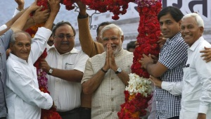 Hindu nationalist Narendra Modi, the prime ministerial candidate for the main opposition Bharatiya Janata Party (BJP), gestures as he receives a garland from his supporters during a public meeting in Vadodara, in the Gujarat, May 16, 2014. REUTERS/Amit Dave