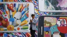A man uses his mobile phone in front of a giant advertisement promoting Samsung Electronics' new Galaxy S5 smartphone, at an art hall in central Seoul April 15, 2014. REUTERS/Kim Hong-Ji/Files