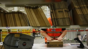 A worker handles items for delivery at Amazon's new distribution center in Brieselang, near Berlin November 28, 2013. REUTERS/Tobias Schwarz/Files