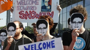 Protesters hold masks depicting former U.S. National Security Agency contractor Edward Snowden during a demonstration in Berlin May 22, 2014. REUTERS/Tobias Schwarz/Files