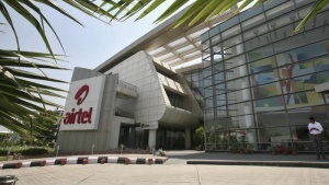 An employee stands in front of the Bharti Airtel zonal office building in Chandigarh May 2, 2013. REUTERS/Ajay Verma/Files