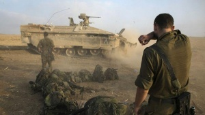 An Israeli soldier stands at a staging area after crossing back into Israel from Gaza July 28, 2014. REUTERS/Baz Ratner