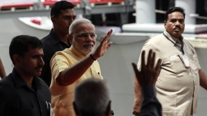 Prime Minister Narendra Modi waves as he leaves after the commissioning ceremony of warship, INS Kolkata at a naval base in Mumbai August 16, 2014. REUTERS/Danish Siddiqui