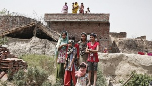 Villagers stand as they watch the house of one of the two teenage girls, who were raped and hanged from a tree, at Budaun district in Uttar Pradesh May 31, 2014. REUTERS/Anindito Mukherjee/Files