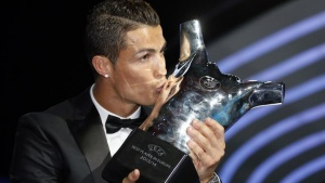 Real Madrid's Cristiano Ronaldo kisses his Best Player UEFA 2014 Award during the draw ceremony for the 2014/2015 Champions League Cup soccer competition at Monaco's Grimaldi Forum in Monte Carlo August 28, 2014. REUTERS/Eric Gaillard