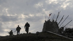 Pro-Russian separatists walk at a destroyed war memorial on Savur-Mohyla, a hill east of the city of Donetsk, August 28, 2014. REUTERS/Maxim Shemetov