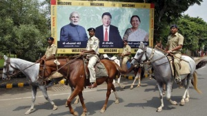 Police personnel patrol on their horses past a boarding with images of (L-R) Prime Minister Narendra Modi, China's President Xi Jinping and Anandiben Patel, Chief Minister of Gujarat, ahead of Xi's arrival in Ahmedabad September 16, 2014. REUTERS/Amit Dave