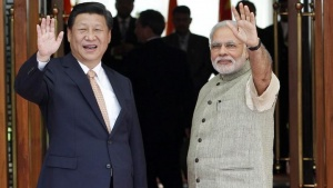 Prime Minister Narendra Modi (R) and China's President Xi Jinping wave before their meeting in Ahmedabad September 17, 2014. REUTERS/Amit Dave