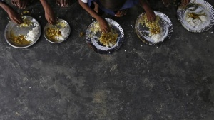 Schoolchildren eat their free mid-day meal, distributed by a government-run primary school at Brahimpur village in Chapra district of Bihar July 19, 2013. REUTERS/Adnan Abidi/Files