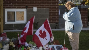 A woman pays respects at a makeshift memorial in honour of Cpl. Nathan Cirillo, outside the Cirillo family home in Hamilton, October 24, 2014.REUTERS/Mark Blinch