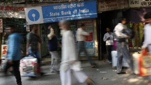 Commuters walk past a State Bank of India branch in the old quarters of Delhi November 13, 2013. REUTERS/Mansi Thapliyal/Files